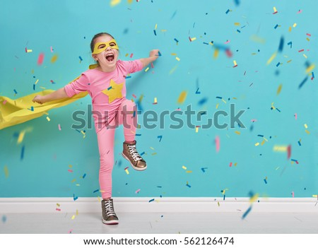 Little child plays superhero. Kid on the background of bright blue wall. Girl is throwing confetti and jumping. Yellow, pink and  turquoise colors. #562126474