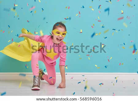 Little child plays superhero. Kid on the background of bright blue wall. Girl is throwing confetti. Yellow, pink and  turquoise colors. #568596016