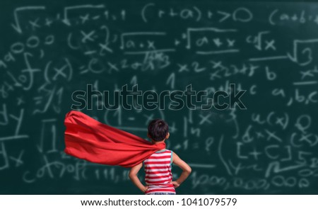 Little child plays superhero. Kid on the background of chalkboard background. Education and success concept. Asia kid Learning Art Mathematics Formula.