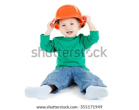 4eef8f313aa Little child plays with orange construction protective helmet on white  background. Profession future builder.