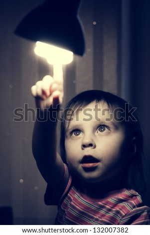 Little child points his finger at a lighted lamp.