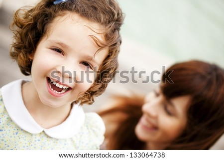 Little child portrait, with her smiling mother in a second term