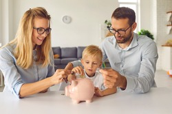 Little child puts money inside piggy bank, learns to effectively manage budget and spend wisely from young independent parents able to provide high living standard. Kids financial literacy concept