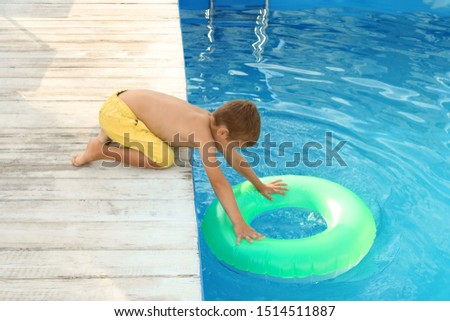 Little child reaching for inflatable ring in outdoor swimming pool. Dangerous situation