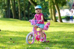 Little child riding her bicycle in the park. Cute preschooler girl learning to cycle with stabilisers wheels. Sportive kid enjoying sunny summer, spring or autumn day outdoors.