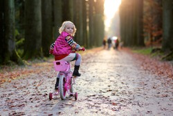 Little child riding her bicycle in the park. Cute preschooler girl learning to cycle with stabilisers wheels. Sportive kid enjoying sunny day outdoors in the forest.