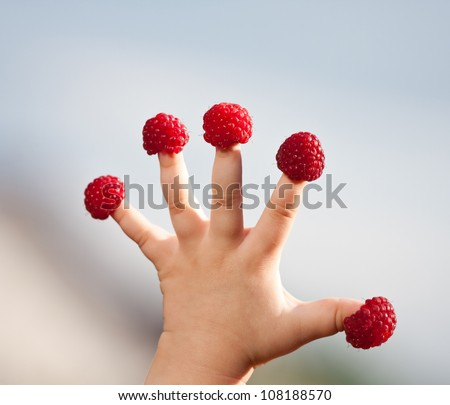 "Little child's hand with raspberry ""hats"" on fingers"