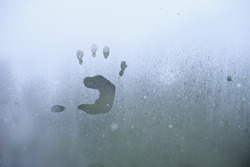 Little child's handprint on foggy rainy glass.