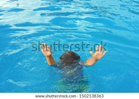 Little child sinking in outdoor swimming pool. Dangerous situation