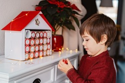 Little child taking chocolate opening first day in handmade advent calendar made from toilet paper rolls. Sustainable Christmas, upcycling, zero waste, kids seasonal activities