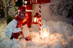 Little child, toddler boy, sending letter to santa in christmas mailbox, christmas decoration around him, outdoor snow shot