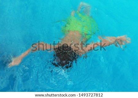 Little child under water in outdoor swimming pool. Dangerous situation