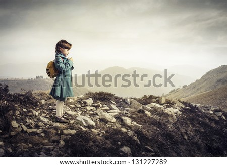 little child with backpack in the mountain