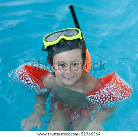 Little child with diving goggles and snorkel swimming in the water
