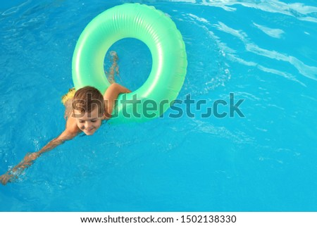 Little child with inflatable ring in outdoor swimming pool. Dangerous situation