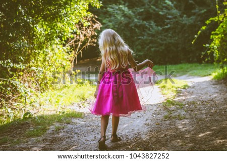 little child with long blond hair dressed in pink dress walking in the forest back to camera #1043827252