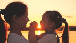 Little child with mom plays at sunset in the sky. Happy mother and daughter admire the sunrise. Family life concept. Teamwork. Girl with a young woman in the glare of the sun. Love for children