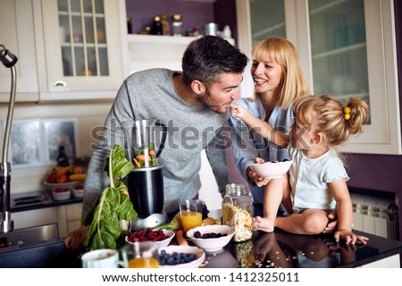 Little child with parents having fun during breakfast