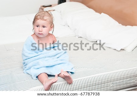 Little child wrapped in a towel sitting on bed after washing grimy