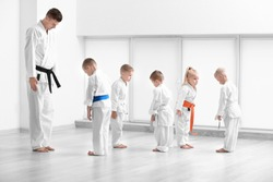 Little children and instructor performing ritual bow prior to practicing karate in dojo