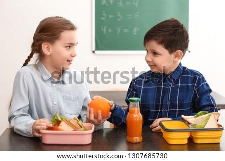 Little children having lunch in classroom