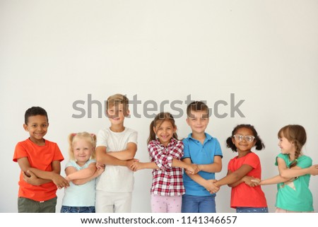 Little children holding hands on light background. Unity concept #1141346657