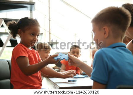 Little children holding puzzle pieces in hands, indoors. Unity concept #1142639120