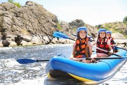 Little children kayaking on river. Summer camp