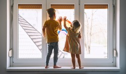 Little children on background of painting rainbow on window. Photo of kids leisure at home. Positive visual support during quarantine Pandemic Coronavirus Covid-19 at home. Family background