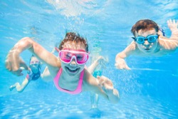 little children  playing and  swimming  in pool  under the water.