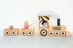 Little children playing with cardboard train in light room