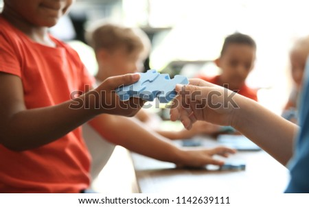 Little children playing with puzzle indoors, focus on hands. Unity concept #1142639111