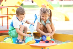 Little children playing with toys in sand box outdoors