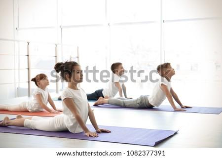 Little children practicing yoga in gym