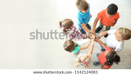 Little children putting their hands together indoors, top view. Unity concept #1142124083