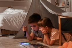 Little children reading bedtime story at home