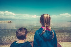 Little children standing on the shore and looking in admiration on Lake Ohrid, Republic of Macedonia