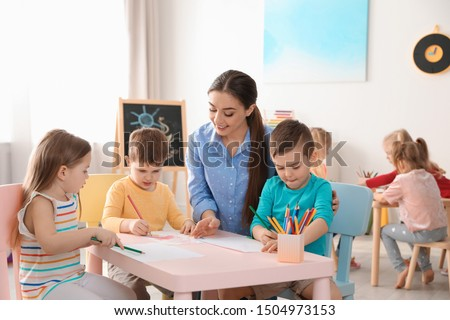 Little children with kindergarten teacher drawing at table indoors. Learning and playing