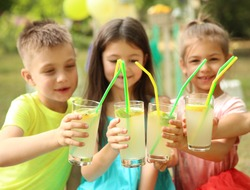 Little children with natural lemonade in park