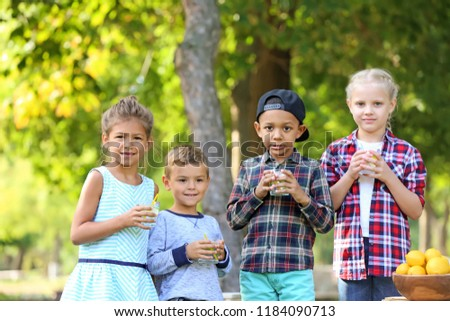 Little children with natural lemonade resting in park #1184090713