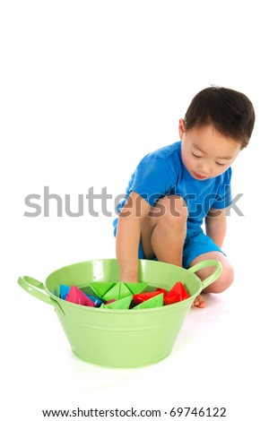 Little Chinese boy is playing with paper boats isolated over white