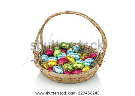 Little chocolate eggs in a basket with straw