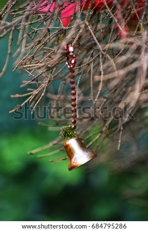 Little Christmas bell on the withered branch close up photo #684795286