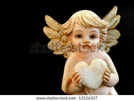 Little chritsmas or valentine angel with wings is holding a heart in ...