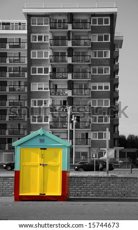 Little colorful beach hut on Brighton and Hove promenade with black and white high rise building contrasting in the background