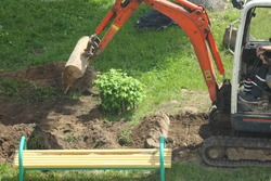 Little compact crawler excavator on rubber tracks carefully digs a ditch with a bucket in the Park on a summer day against the background of green grass, bushes and benches, local landscaping works