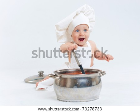 Little cook. Cute little boy in a suit of Food Boy with kitchen accessories. In the studio