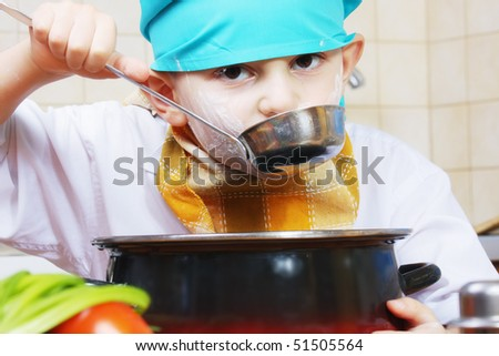 Little cook in green cap testing food from ladle