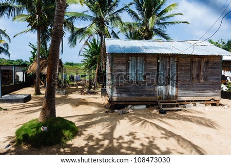 LITTLE CORN ISLAND, NICARAGUA: Little wooden house among palm trees and shadows on the beach on a sunny day