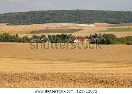 Little countryside village in northern France with harvested wheat fields